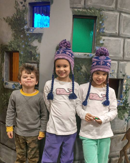 Three siblings, twin girls in matching snow caps and their younger brother, smile for the camera at Dentistry for Children.